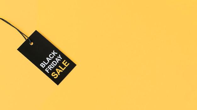 Etiqueta preta de venda na sexta-feira sobre fundo amarelo do espaço