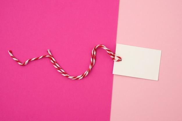Etiqueta retangular de papel branco em uma corda em um fundo colorido