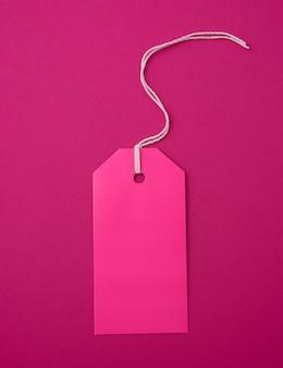 Etiqueta retangular de papel rosa vazio em uma corda em um fundo rosa