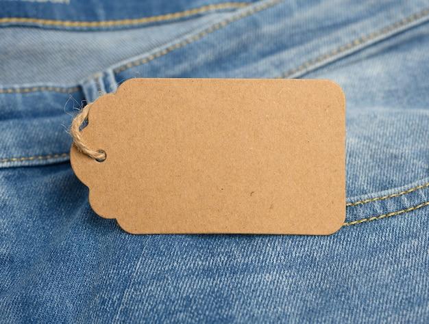 Etiqueta retangular de papelão em branco amarrada a jeans azul, close-up