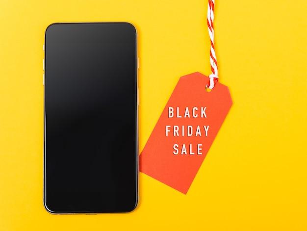 Etiqueta vermelha do texto de venda da black friday para compras online e tela em branco do smartphone