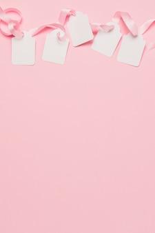 Etiquetas brancas e fita rosa na parte superior do fundo com espaço para texto