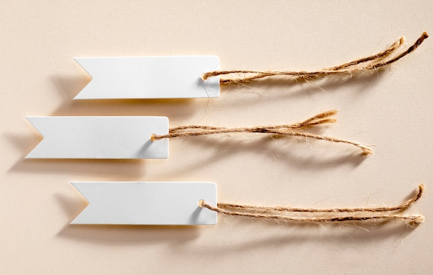 Etiquetas brancas vazias de vista lateral em fundo bege