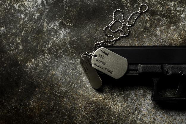 Etiquetas de cão militares em branco e uma arma na placa de metal enferrujada abandonada.