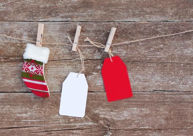 Etiquetas de papel branco e vermelho e meias de natal penduradas em uma corda com prendedores de roupa