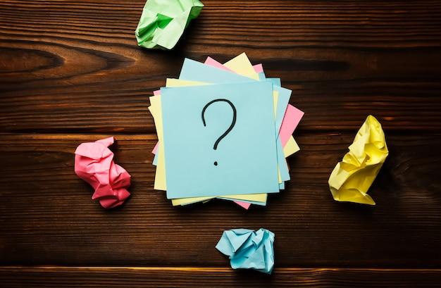 Etiquetas de papel com um ponto de interrogação em um fundo de madeira