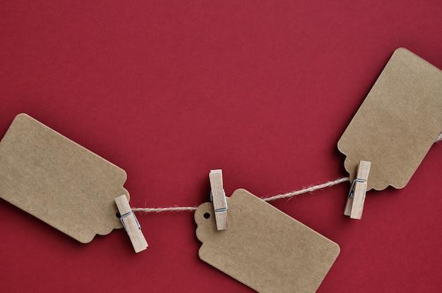 Etiquetas de papel são presas com prendedores de roupa à corda em vermelho.