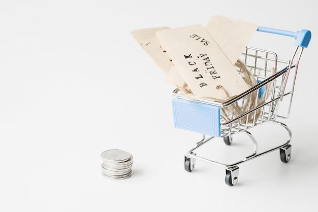 Etiquetas no carrinho de compras perto de moedas