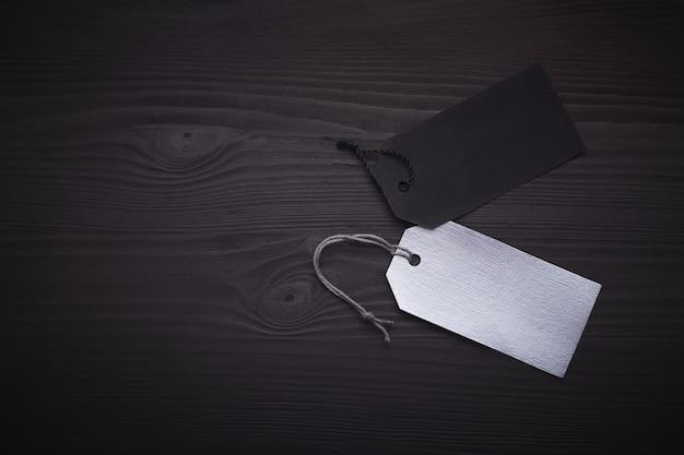 Etiquetas pretas e prata em branco no preto de madeira.