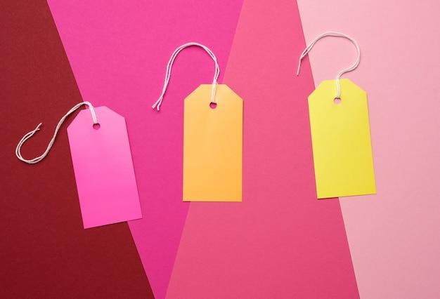 Etiquetas retangulares de papel em uma corda em um fundo colorido