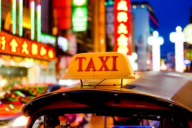 Etiquete o nome do carro de tuk tuk ou do táxi tailândia na estrada de yaowarat na cidade de china em banguecoque na noite.