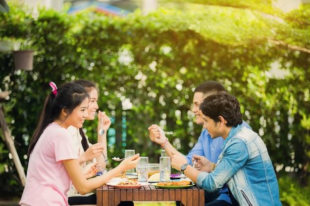 Etnia asiática que come o café da manhã no jardim em casa. todos riram e curtiram