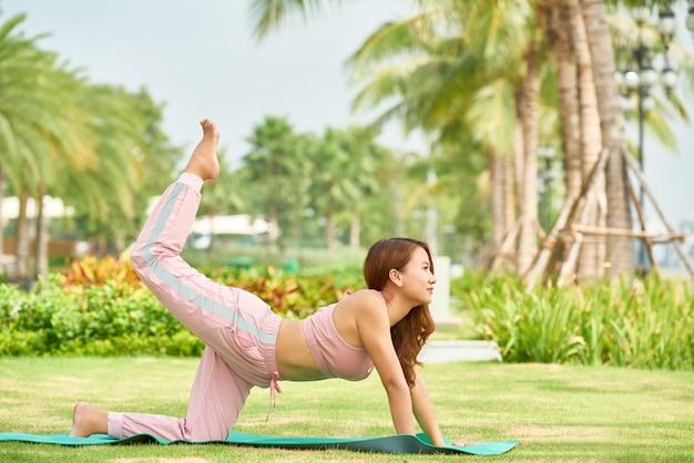 Étnica mulher fazendo yoga no parque