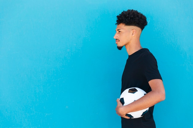 Étnico homem com cabelo encaracolado em pé com futebol