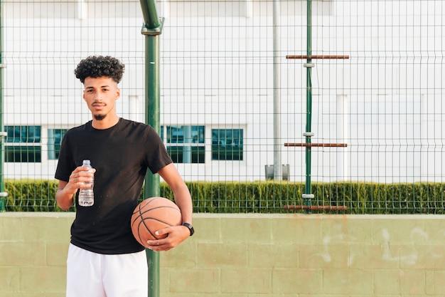 Étnico jovem macho segurando o basquete na quadra