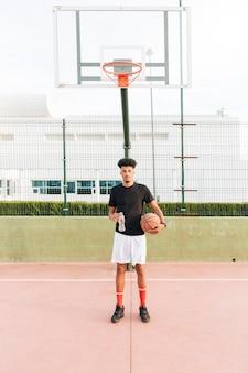 Étnico jovem segurando o basquete na quadra