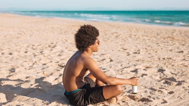 Étnico masculino sentado na praia segurando cerveja