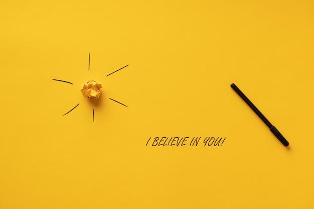 Eu acredito em você assina soletrado com hidrocor preto sobre fundo amarelo ao lado do sol.