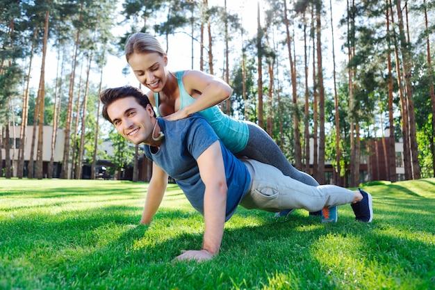 Eu acredito em você. jovem alegre sorrindo enquanto ajudava o namorado a fazer flexões
