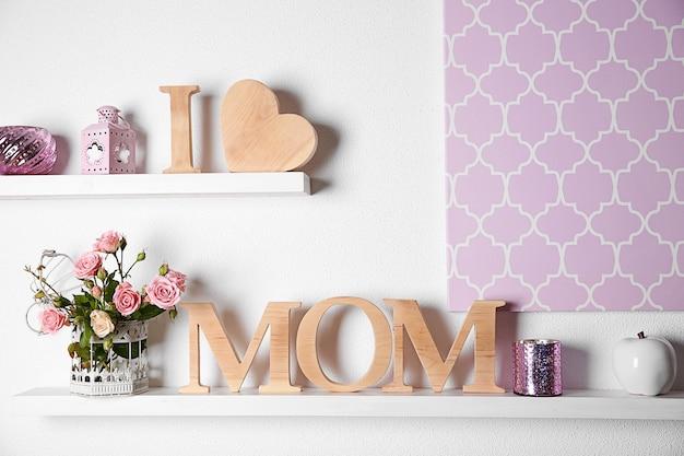 Eu amo a inscrição da mãe de letras de madeira com coração e flores no fundo da parede branca