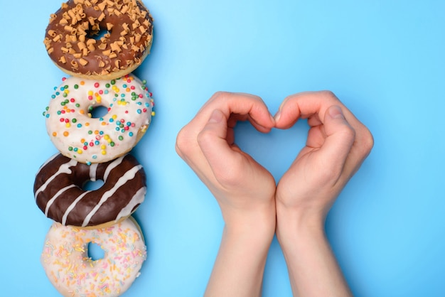 Eu amo comer o conceito de donuts. foto de vista aérea plana lay top de quatro objetos de comida em uma fileira e criança criança fazendo coração com fundo pastel de mãos isoladas