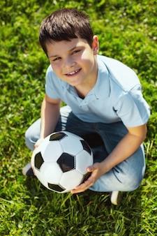 Eu amo futebol. menino alegre de cabelos escuros sorrindo e sentado com sua bola de futebol