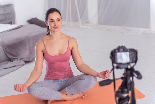 Eu amo ioga. blogueira atraente, alegre, de cabelos escuros, sorrindo e fazendo ioga no tapete enquanto faz um vídeo para seu blog