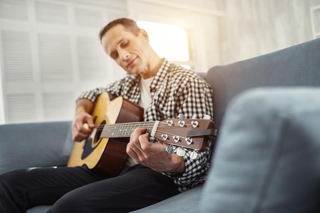 Eu amo jogar. homem bonito e bem construído, sorrindo e tocando violão enquanto está sentado no sofá
