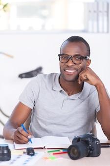 Eu amo meu trabalho! africano jovem alegre em uso casual escrevendo algo no bloco de notas e olhando para a câmera enquanto está sentado em seu local de trabalho