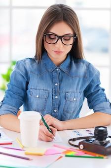 Eu amo meu trabalho! jovem empresária alegre em uso casual escrevendo algo no bloco de notas enquanto está sentado em seu local de trabalho