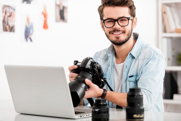 Eu amo meu trabalho! jovem feliz segurando a câmera e sorrindo enquanto está sentado em seu local de trabalho