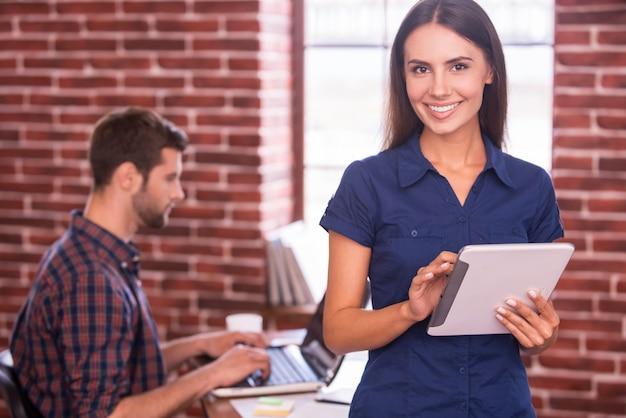 Eu amo meu trabalho! mulher jovem e bonita segurando um tablet digital e sorrindo enquanto o homem está sentado no fundo e trabalhando no laptop