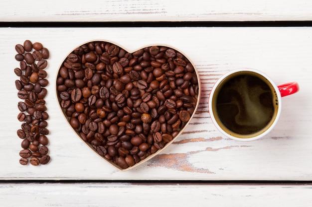 Eu amo o conceito de café forte e fresco. sementes de café torrado em forma de letra i e coração. superfície de pranchas de madeira brancas.