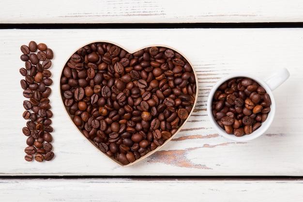 Eu amo o conceito de café fresco natural. sementes de café dispostas em forma de coração e copo de recheio. superfície de madeira branca.