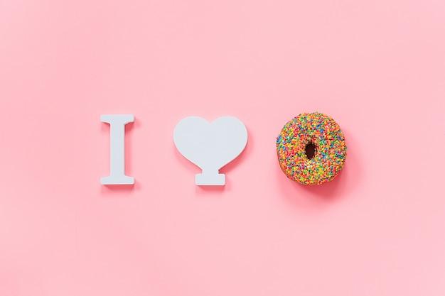 Eu amo o conceito de rosquinhas. rosquinha multicolorida e coração branco em uma parede rosa