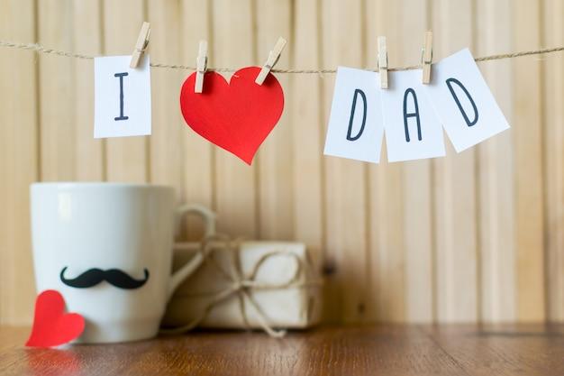 Eu amo o papai. saudação de dia dos pais. mensagem com o coração de papel que pendura com os pregadores de roupa sobre a placa de madeira.