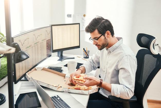 Eu amo pizza, jovem empresário barbudo ou comerciante de óculos e roupas formais está comendo