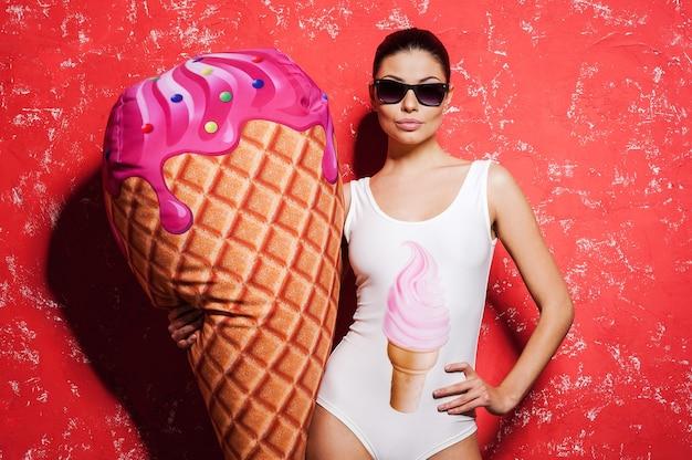 Eu amo sorvete! mulher jovem e bonita com óculos escuros e roupas descoladas segurando um enorme sorvete falso em pé contra um fundo vermelho