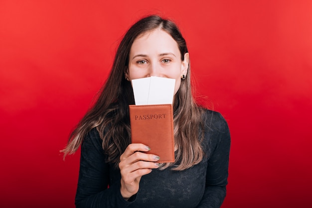 Eu amo viajar. jovem mulher está cobrindo metade do rosto com passaporte e alguns bilhetes no espaço vermelho.