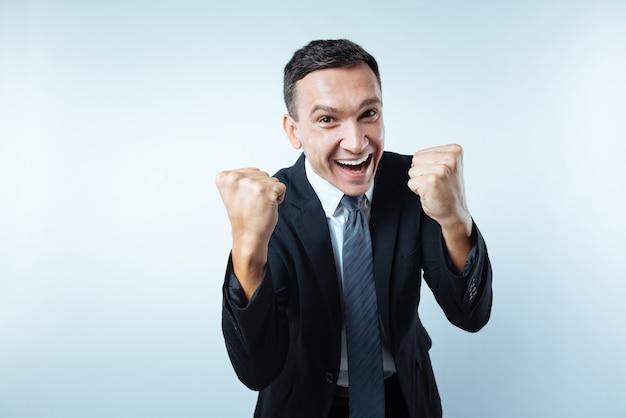 Eu digo sim. feliz alegre bom empresário segurando os punhos e rindo enquanto expressa sua felicidade