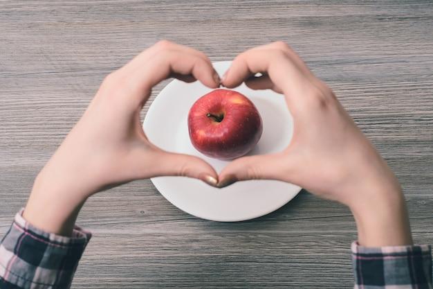 Eu escolho comida saudável! foto em close-up das mãos de uma mulher fazendo uma moldura em formato de coração com os dedos com uma maçã no centro da moldura. eu escolho uma alimentação saudável!