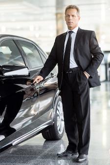 Eu escolho este carro. comprimento total de um empresário de cabelo grisalho maduro em pé perto do carro e segurando a maçaneta da porta na concessionária