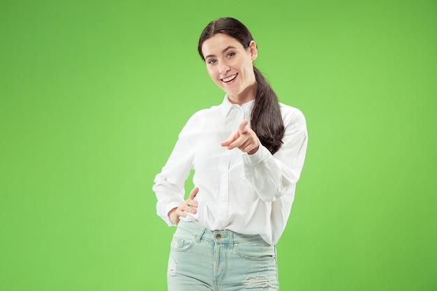 Eu escolho você e faço o pedido. a sorridente mulher de negócios aponta para você, quero você, retrato em close-up de meio comprimento no espaço verde