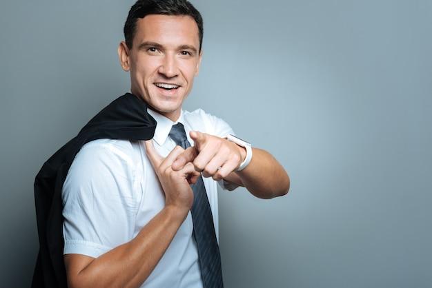 Eu escolho você. homem bonito encantado positivo sorrindo e apontando para você enquanto segura sua jaqueta