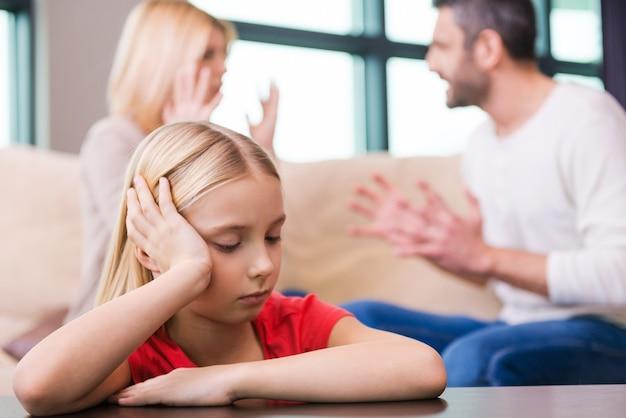 Eu espero que eles resolvam isso. menina triste encostada na mesa e segurando a cabeça na mão enquanto os pais gritam um com o outro ao fundo
