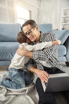 Eu estimo você. pai bonito e exuberante de cabelos escuros sentado no chão trabalhando em seu laptop e seu filho o abraçando