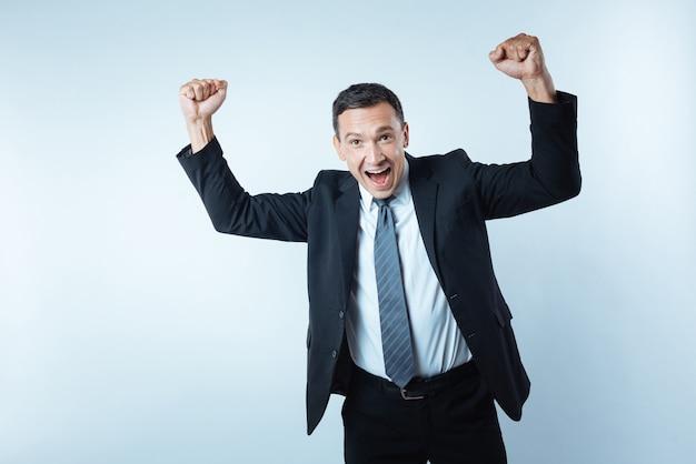 Eu estou feliz. homem alegre e encantado com os braços erguidos e mostrando sua felicidade ao fazer um negócio bem-sucedido