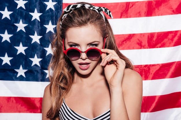 Eu estou observando você. mulher jovem e bonita olhando por cima dos óculos de sol em pé contra a bandeira americana
