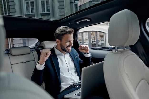 Eu fiz isso homem jovem bonito de terno completo gesticulando e sorrindo enquanto está sentado no carro