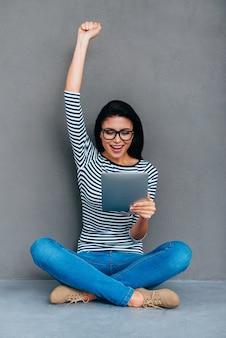 Eu fiz isso! mulher jovem feliz segurando um tablet digital e mantendo o braço levantado enquanto está sentado no chão e contra um fundo cinza